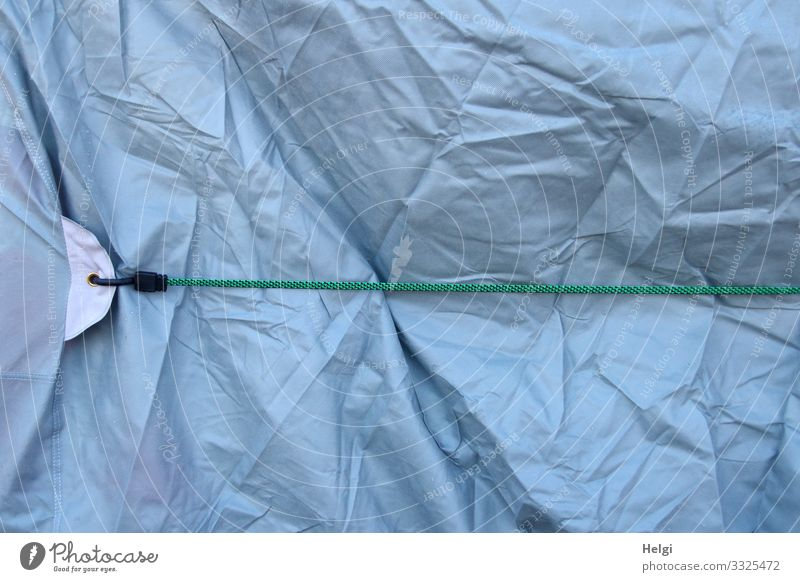 short tied | literally - light blue wrinkled plastic tarpaulin is held in place with a rubber band Rubber elastic band stop To hold on connected crease