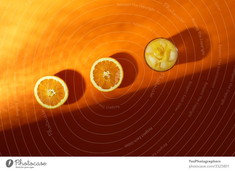 Cold orange juice glass and orange cut in half in sunlight Fruit Orange Breakfast Beverage Cold drink Glass Fresh above view citrous Citrus fruits colorful