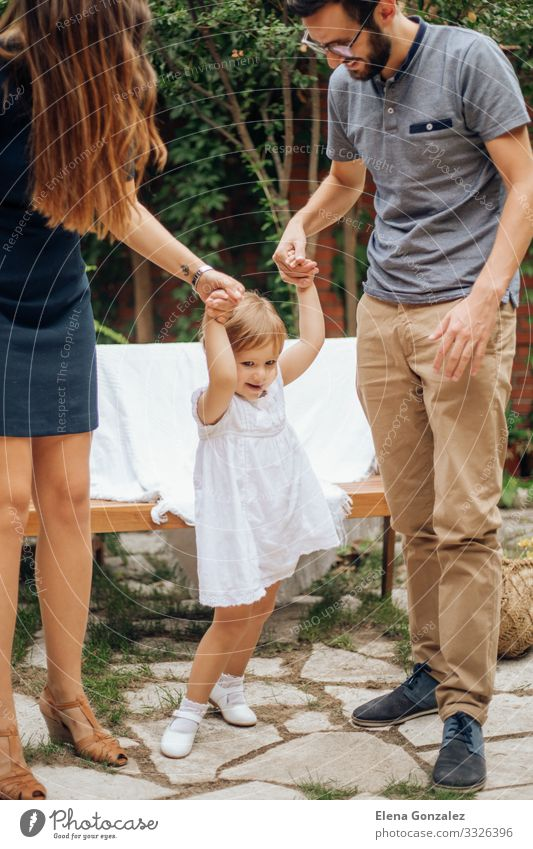 Little blonde girl playing and holding her young parents hand. Playing Freedom Garden Wedding Parenting Child Baby Man Adults Parents Mother Father