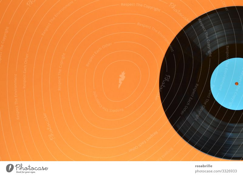 old vinyl record on orange background with free space left also makes a nice | sound Record Records. LP Ancient vintage Music Disco Black long-playing record