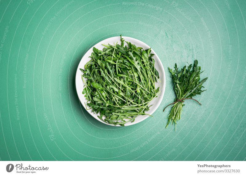 Arugula salad and arugula bundle on green table. Fresh herbs Vegetable Lettuce Salad Vegetarian diet Diet Healthy Eating Garden Gardening Plant Hip & trendy