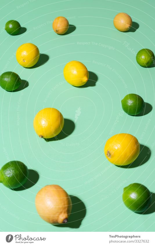 Lemons and limes fruits on a green background. Summer fruits Food Fruit Breakfast Beautiful weather Fresh aqua menthe cheerful Citrus fruits colorful