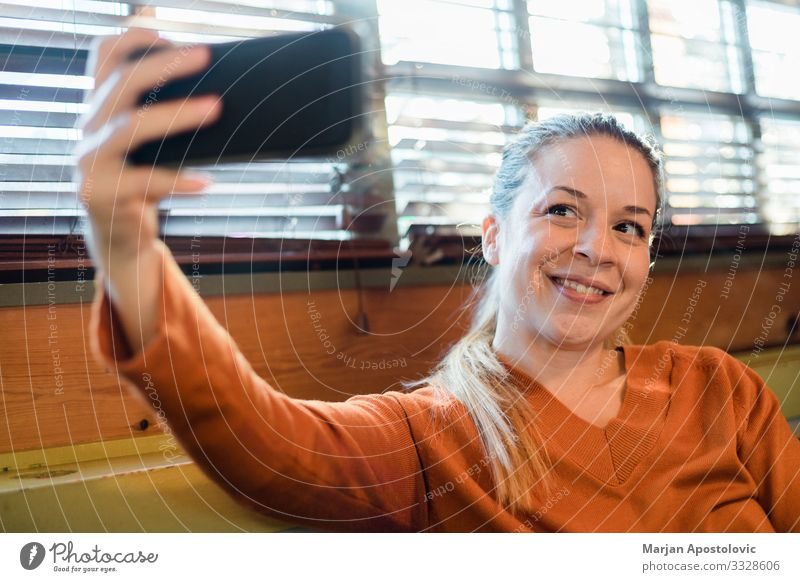 Young woman taking a selfie indoors by the window Lifestyle Joy Cellphone Camera Technology Telecommunications Internet Feminine Youth (Young adults) Woman