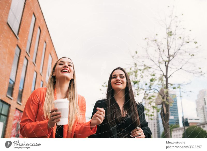 Two young friends walking together outdoors. Lifestyle Style Joy Happy Vacation & Travel To talk Human being Feminine Woman Adults Friendship Town Street