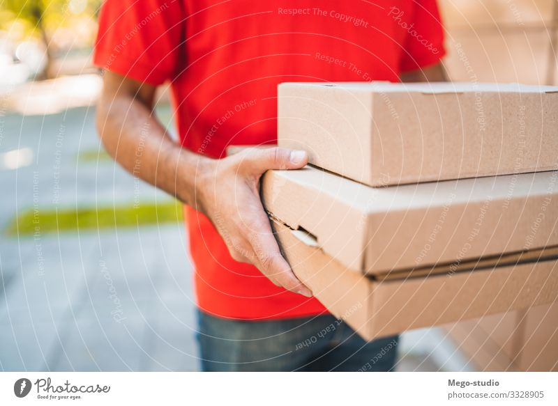 Delivery man carrying packages while making home delivery. Work and employment Profession Craftsperson Office Industry Business Human being Man Adults Hand 1
