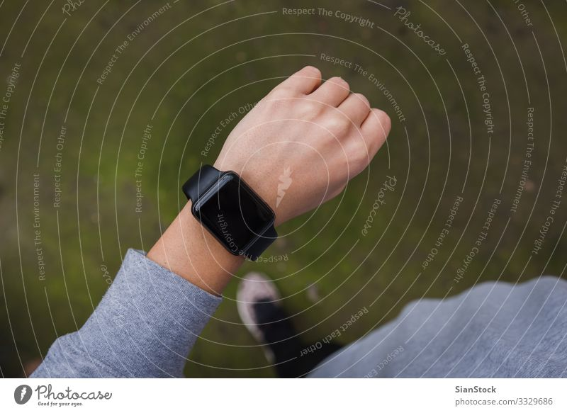 Close up of young woman checking the smartwatch, outdoors. Lifestyle Winter Sports Jogging Screen Technology Human being Woman Adults Hand Autumn Heart Observe