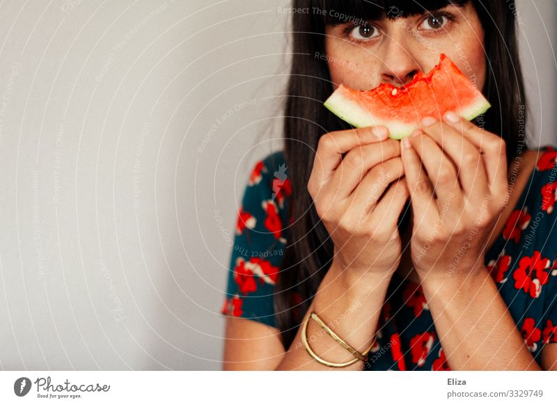A young woman with colorful clothes and brown hair holds a bitten piece of watermelon in front of her mouth/face Human being Feminine Young woman
