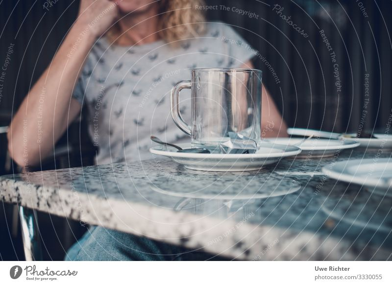 Fau at a table behind an empty teacup To have a coffee Tea Cup Glass Spoon Contentment To enjoy Colour photo Exterior shot Day Shallow depth of field