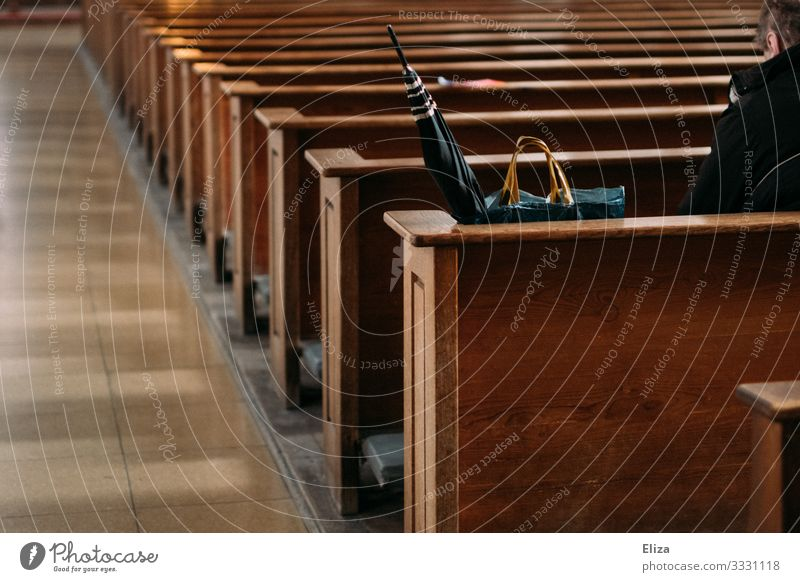 A man sits lonely and alone beside his umbrella and shopping bag on a pew in the church and prays Church Human being Church pew Sit Lonely by oneself Bench