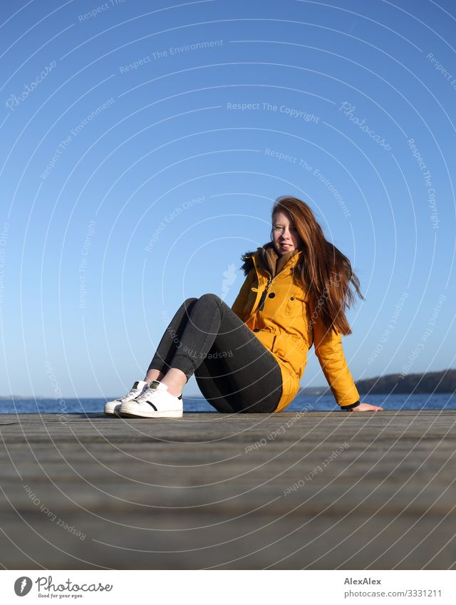 Young woman sitting on a jetty by the sea Lifestyle Joy Beautiful Well-being Vacation & Travel Trip Ocean Footbridge Wooden floor Youth (Young adults)