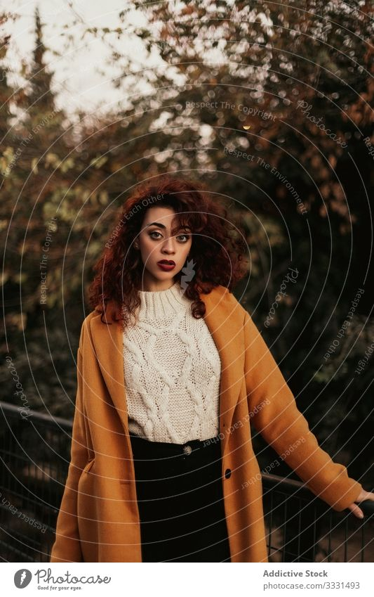 Pensive curly haired woman wearing casual standing in park pensive sensual young dark hair overcoat jumper railing knitted female thoughtful thinking trendy