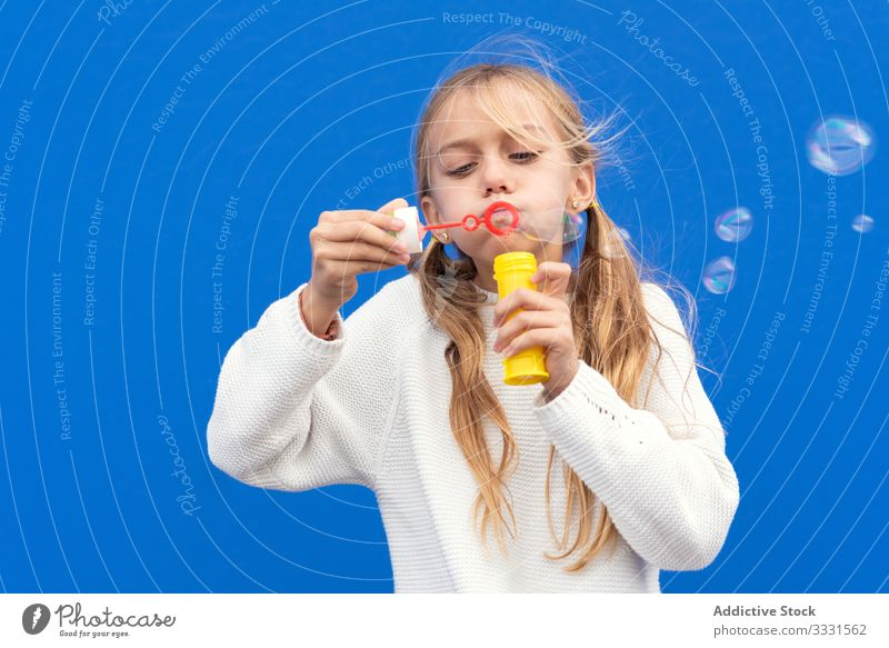 Funny girl blowing soap bubbles playful kid fun smile laugh casual little childhood hand carefree happiness beautiful open mouth excited cheerful female