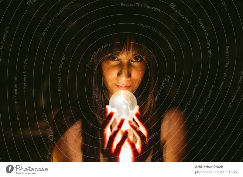 Thoughtful woman with burning lightbulb in darkness model magic glow bright idea female innovation energy lamp night imagination power invention electricity
