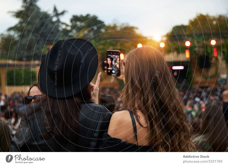 Long haired women taking selfies on smartphone standing in group pf people in sunny day friend photo festival celebration friendship communication together
