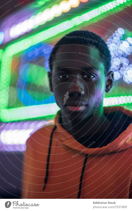 African American guy on funfair man fairground night colorful illumination ethnic modern stylish rest weekend male festive event holiday trendy relax lifestyle