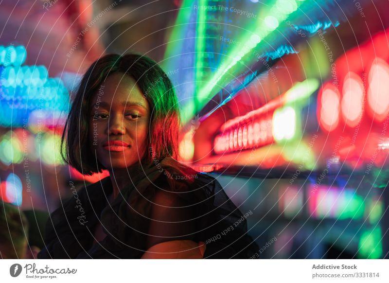 Cheerful black woman on funfair smile night arcade illumination sit rest weekend ethnic female amusement attraction colorful joy happy cheerful bright lady