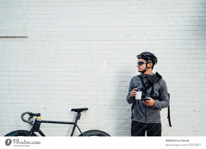 Professional cyclist with smartphone and coffee to go man using browsing bicycle bike city mobile phone street asphalt road equipment eyeglasses male helmet