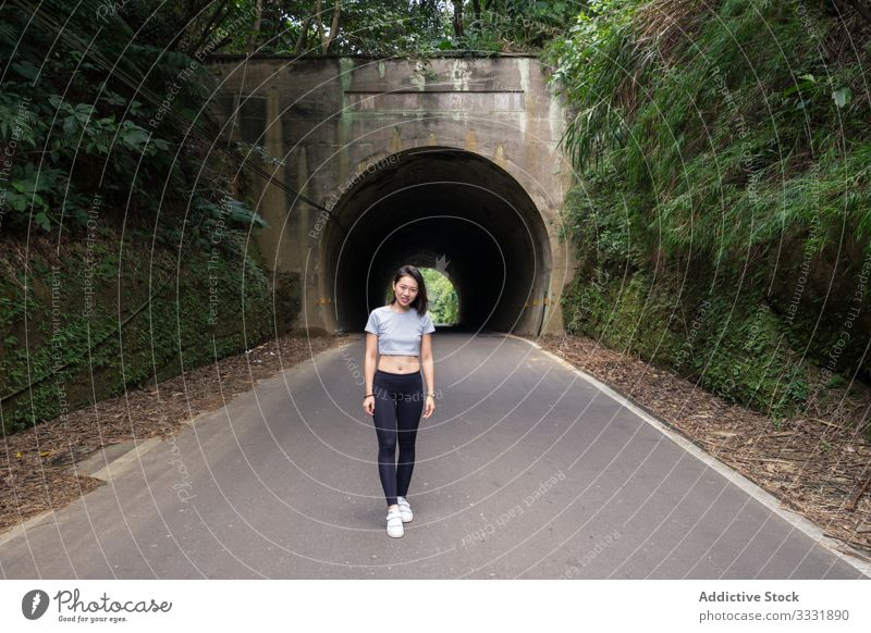 Satisfied female traveler during walk in countryside walking tunnel sportive plants green woman asian young smile laugh enjoy rout road destination explore