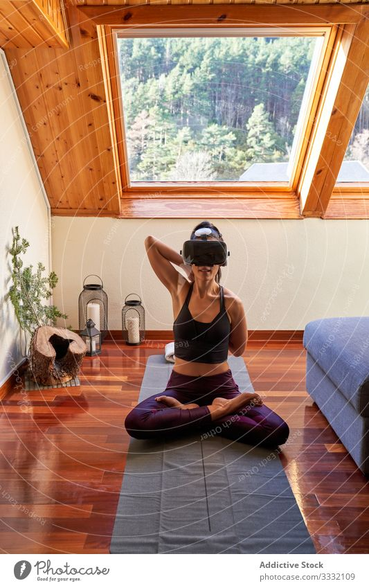 Woman in VR headset meditating at home woman yoga meditation vr exercise room morning lotus pose workout gadget device glasses goggles slim fitness female asana
