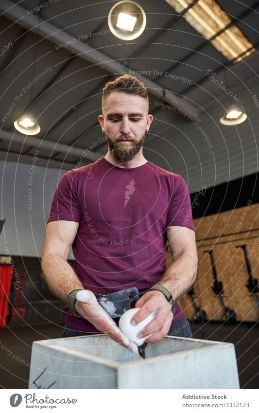 Strong man prepares to exercise in the gym with magnesium in his hands. Young athlete practicing multidisciplinary training weightlifter cross preparing