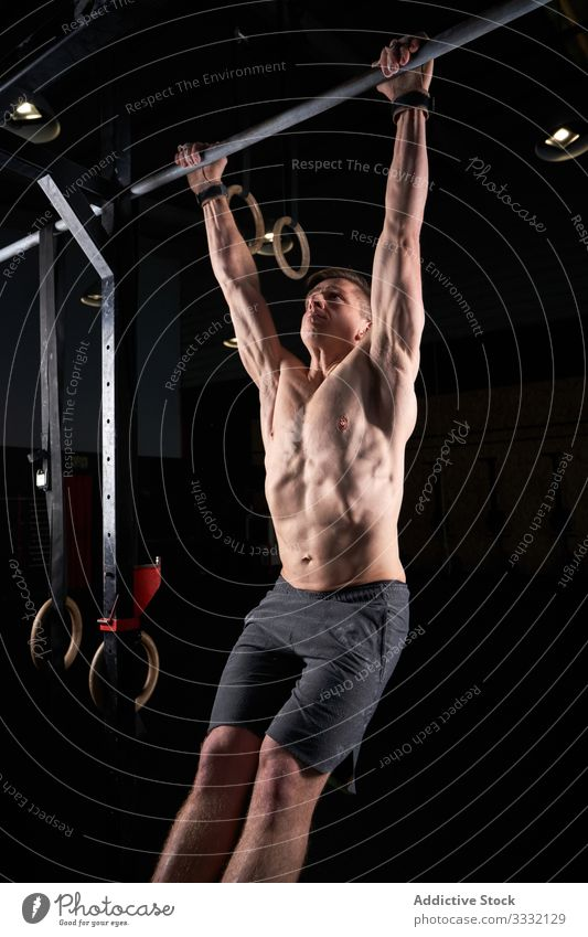 Strong man doing strength exercises on a bar in the gym with magnesium in his hands. Young athlete practicing multidisciplinary training loss weight focus
