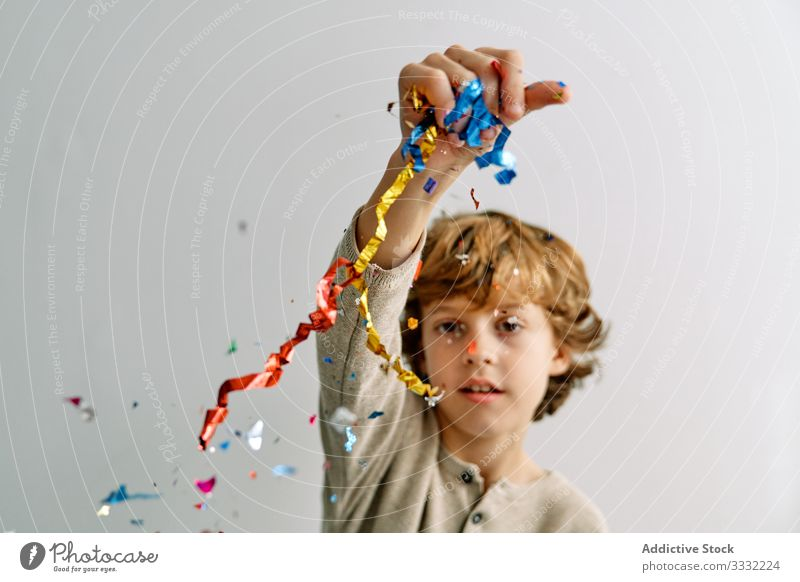Overjoyed boy having fun with confetti at home play toss sitting throw child male teen colorful smile enjoy laugh modern childhood lifestyle celebrate holiday