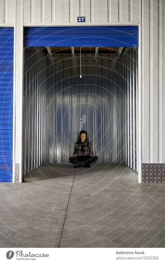 Woman sitting at self storage floor woman package warehouse packing cargo delivery transportation move work relocating packet moving unpacking business
