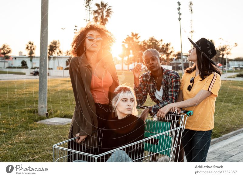 Multiracial group of young women standing around shopping cart on road diverse casual challenge joke empty holding sitting friend team buyer consumerism store