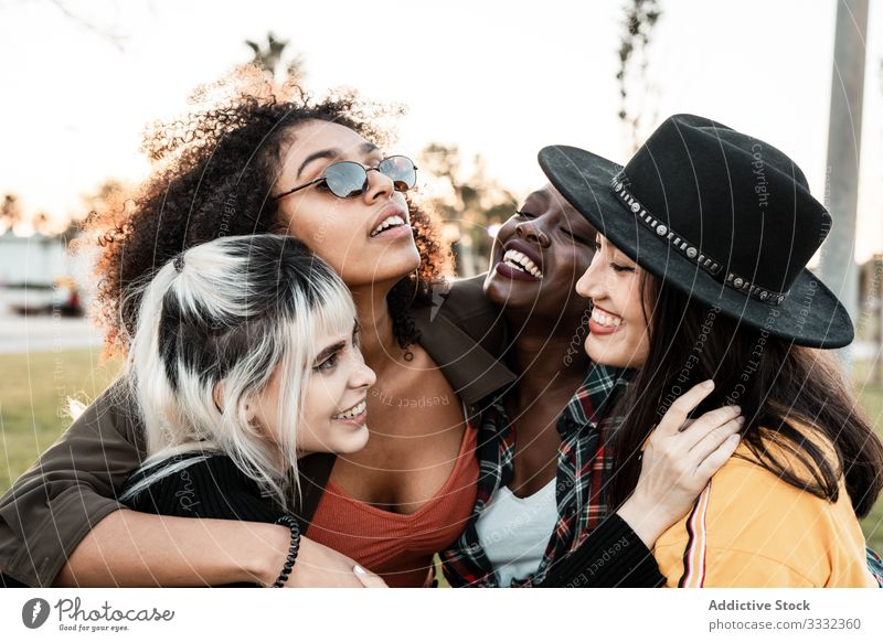 Multiethnic group of female hipsters cuddling with each one young style smile hug portrait together friend diverse multiracial multiethnic hugging laughing