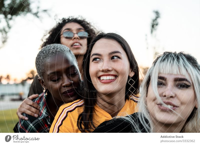 Diverse group of smiling women hugging together on lawn friend laughing cuddling casual fun young female embracing diverse multiethnic multiracial cheerful