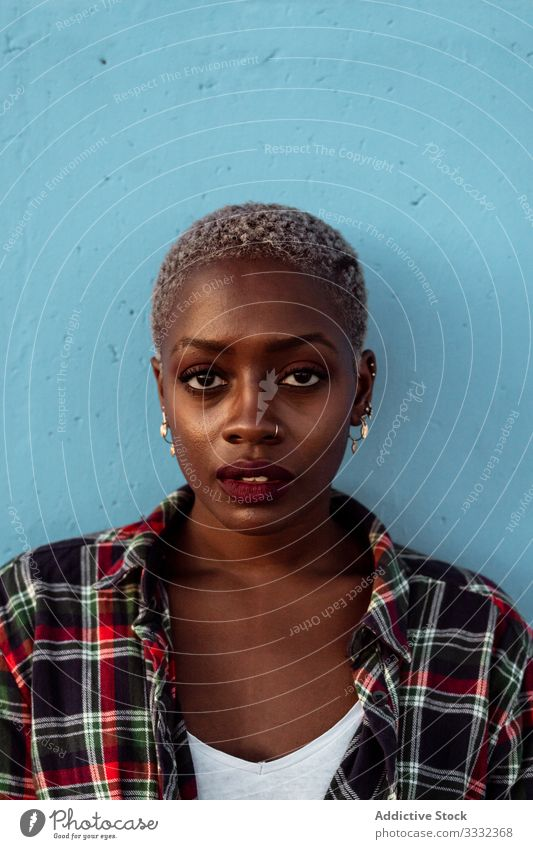 Young black short haired woman looking at camera with intense look female sad portrait challenge piercing plaid shirt african american young unhappy upset
