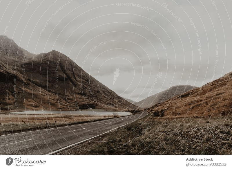 Empty road riding along river surrounded by mountain valley hill travel nature landscape sky tourism adventure gray dangerous extreme journey scenery vacation