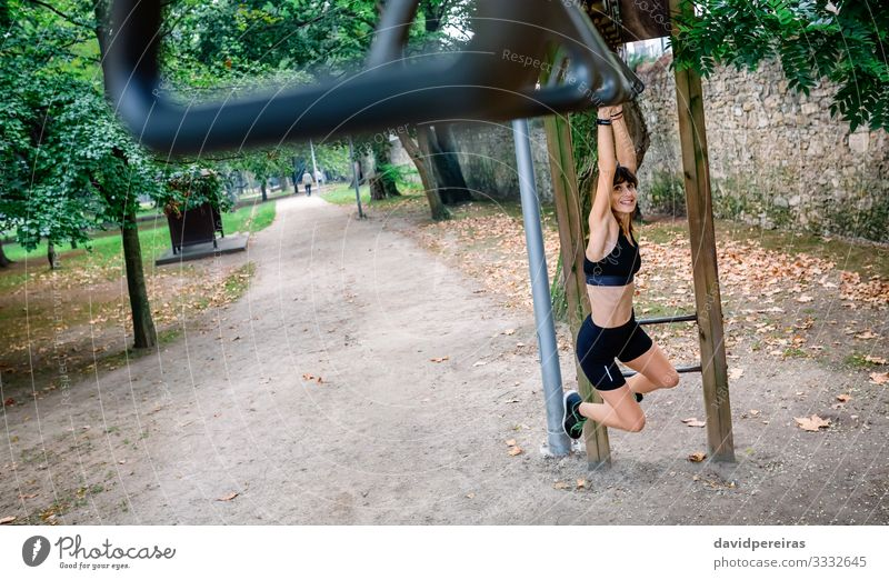 Woman doing monkey exercises on rings Lifestyle Body Sports Human being Adults Tree Park Lanes & trails Sneakers Fitness Smiling Thin Strong Determination