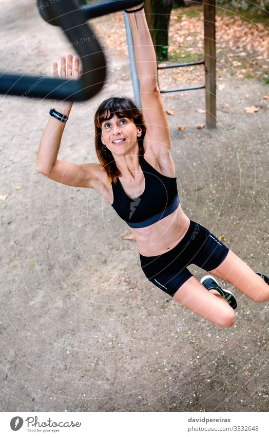 Woman doing monkey exercises on rings Lifestyle Happy Body Sports Human being Adults Park Sneakers Fitness Smiling Thin Strong Determination Effort sportswoman