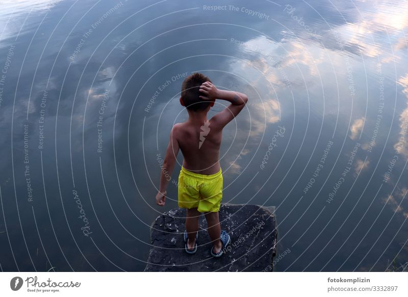 Child looks from a rocky ledge onto a body of water in which the sky is reflected Dream Self-confidence Water Sky Clouds reflection Reflection look at