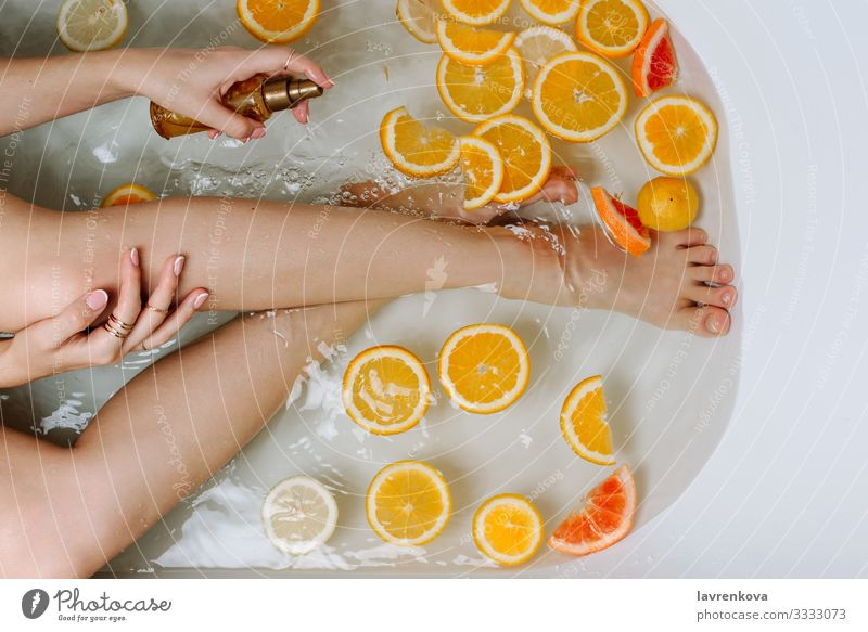 Woman's hand and legs in a bath filled with water Aromatic Swimming & Bathing Bathroom Bathtub Beauty Photography Bomb Bubble care Lemon Citrus fruits Clean