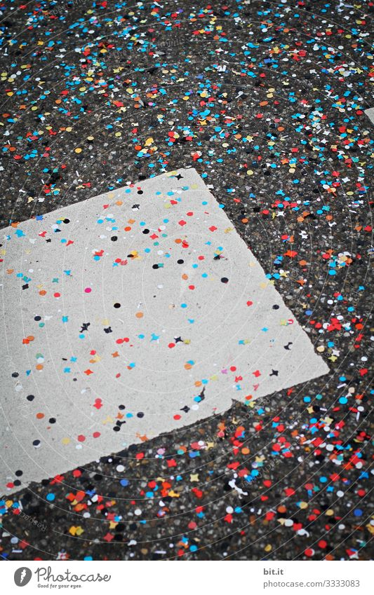 A lot of colorful confetti is spread out at carnival, carnival, fancy dress party, celebration on the gray ground of the street with markings and provides garbage and dirt.