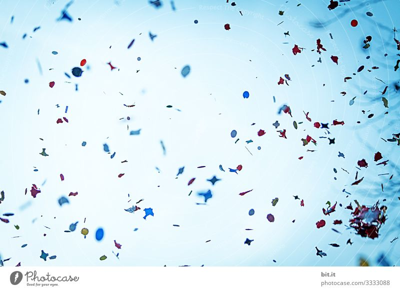 A lot of colourful confetti flies dynamically at carnival, carnival, fancy dress party, celebration in the air, in front of a blue sky and swirls merrily.