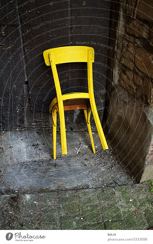 Bright, yellow, old, unused wooden chair, is leaning, tilted, against an old wooden door in an old, abandoned entrance of a stone house/barn. Furniture Chair