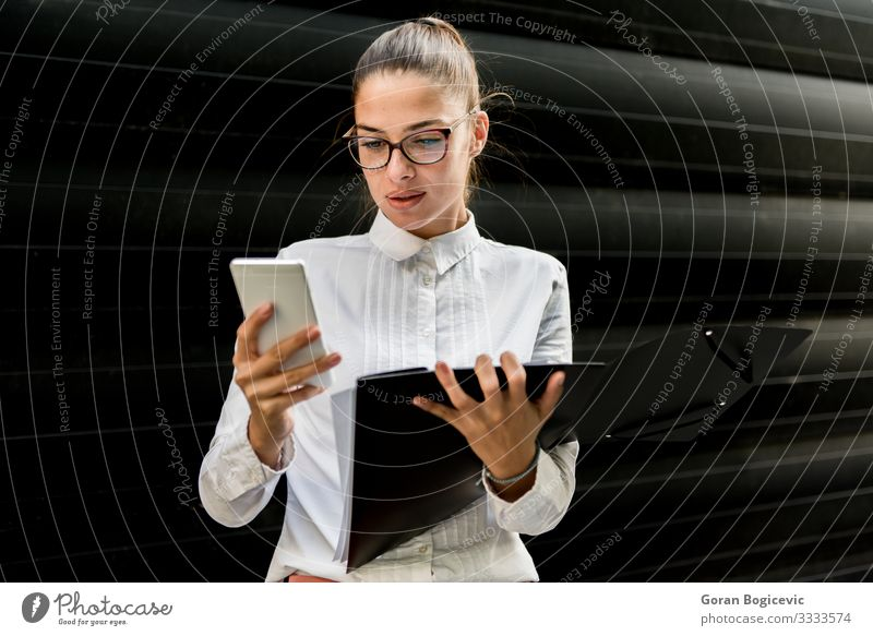 Pretty young businesswoman using mobile phone and holding file Lifestyle Beautiful Work and employment Office Business Telephone PDA Technology Human being