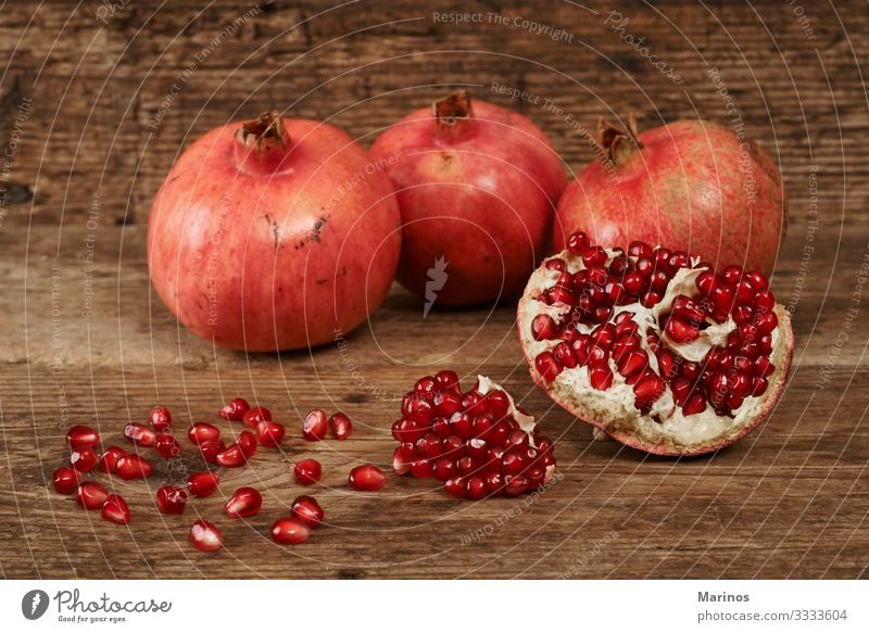 ripe pomegranate fruits on wooden table. Fruit Dessert Vegetarian diet Diet Juice Garden Table Wood Fresh Natural Juicy Red Colour dieting health Vitamin