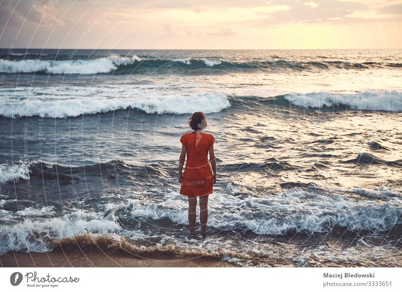 Woman in orange dress standing still in the rough ocean at sunset Lifestyle Relaxation Leisure and hobbies Vacation & Travel Tourism Trip Adventure