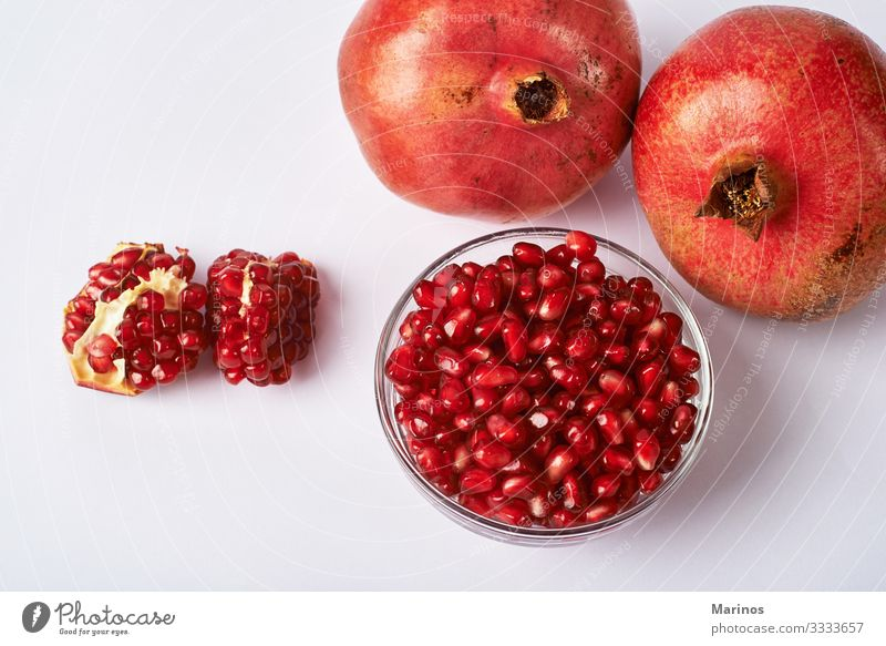 pomegranate fruits and seeds on white background. Fruit Dessert Vegetarian diet Diet Juice Garden Fresh Natural Juicy Red Colour dieting health Vitamin Organic