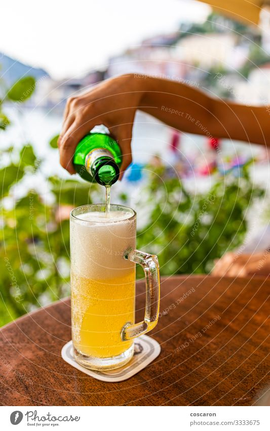 Hand filling a glass of beer on a terrace Beverage Alcoholic drinks Beer Bottle Lifestyle Vacation & Travel Tourism Summer Summer vacation Beach Ocean Table
