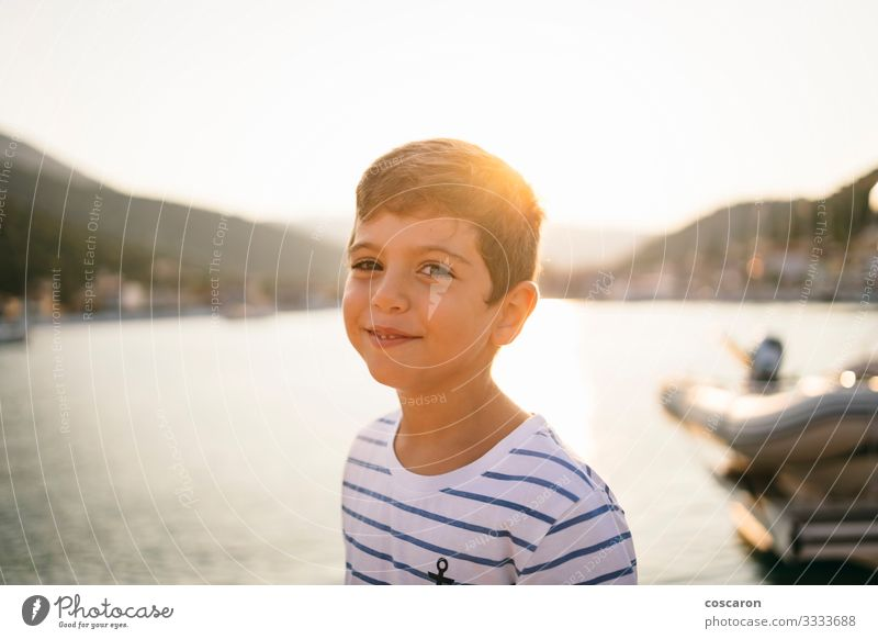 Cute kid smiling at sunset with the sea in the background Lifestyle Joy Happy Beautiful Face Vacation & Travel Tourism Freedom Summer Summer vacation Sun Beach