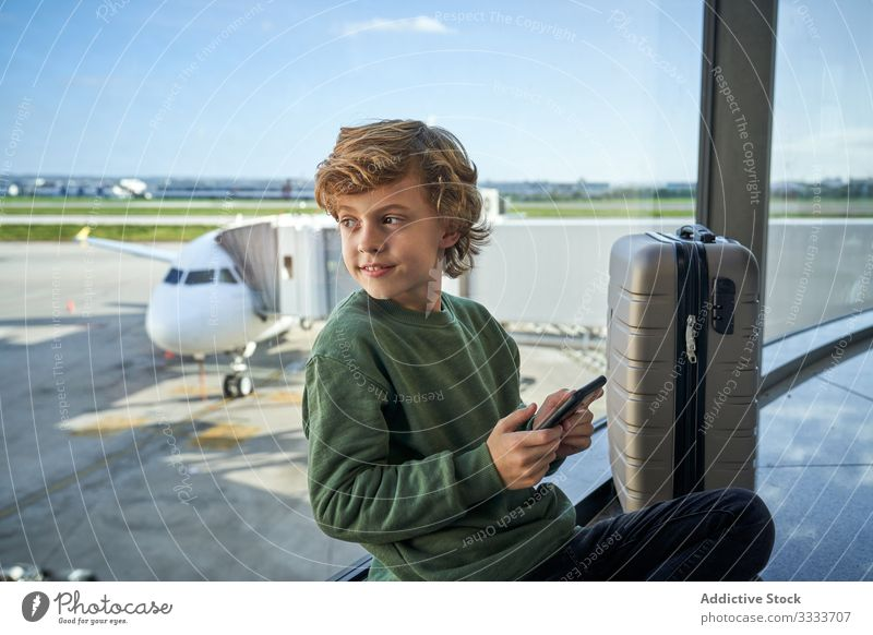 Child using mobile phone in airport child airplane smartphone window modern travel passenger kid aircraft trip transport lifestyle capture moment memory device