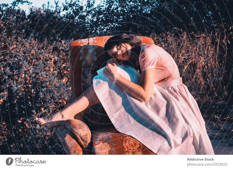 Dreamy female on armchair in countryside woman dreamy concept stylish comfort barefoot dress cute young nature bush shrub think ponder contemplate trendy