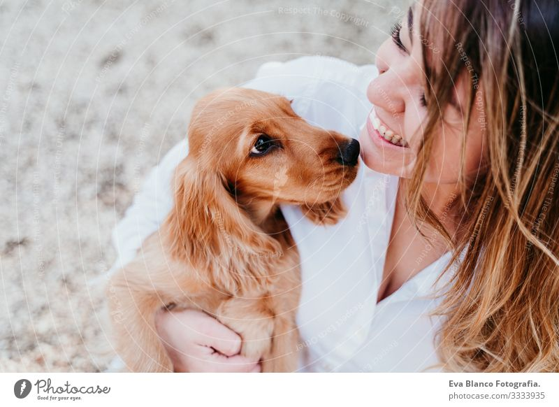 young woman and her cute puppy of cocker spaniel outdoors in a park Woman Dog Pet Park Sunbeam Exterior shot Love Embrace Smiling Rear view Kissing Breed
