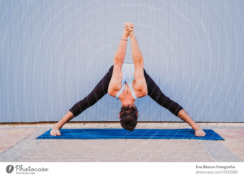 man in the city practicing yoga sport. blue background. healthy lifestyle Blue background Yoga Man City Town Lifestyle Muscular Concentrate