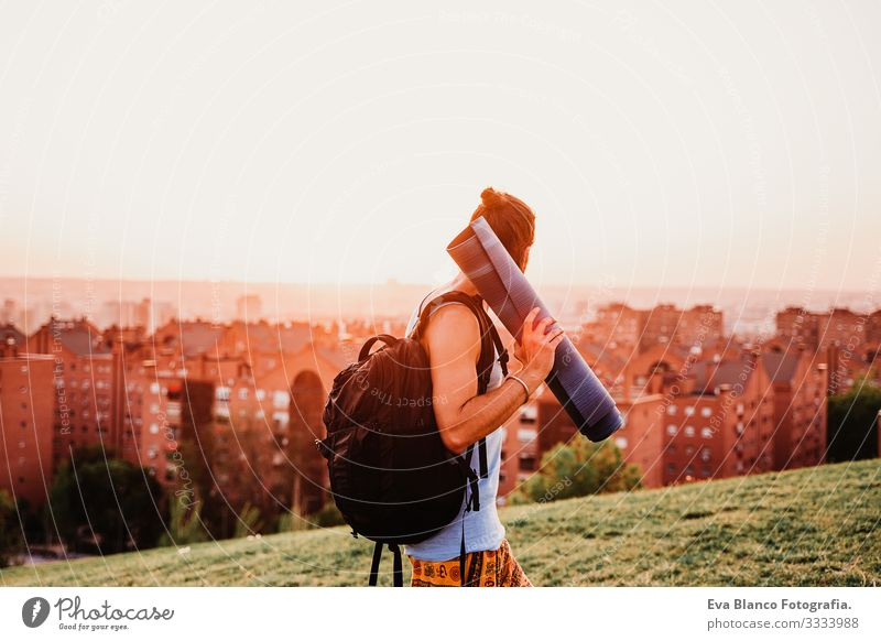 young man in a park ready to practice yoga sport. city background. healthy lifestyle Concentrate Position Human being Youth (Young adults) Body Park Man